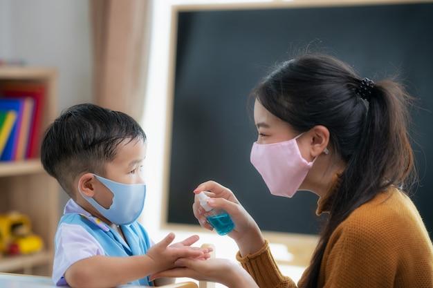 Une enseignante asiatique utilise un spray sur les mains de son élève