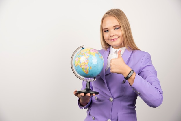 Enseignante avec globe faisant les pouces vers le haut sur blanc.