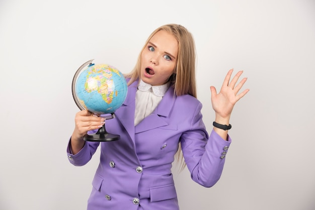 Enseignante avec globe posant sur blanc.