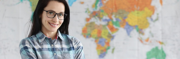 Enseignante avec des lunettes debout sur fond de carte du monde