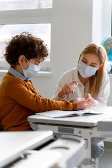 Enseignante avec masque médical désinfectant les mains de l'élève en classe