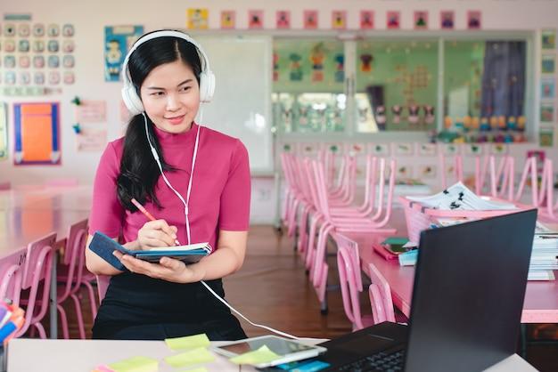 Une enseignante de maternelle asiatique enseigne en ligne aux élèves de la maternelle. les enseignants et les étudiants utilisent des systèmes de vidéoconférence en ligne pour enseigner aux étudiants.