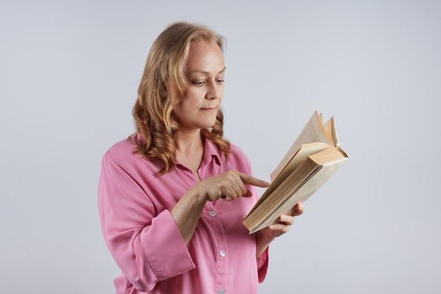 Enseignante mature, bibliothécaire en blouse rose montre le texte du livre avec son doigt. notion d'éducation.