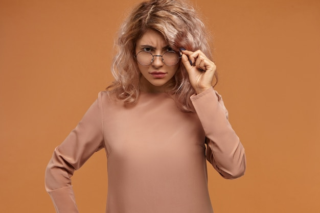 Enseignante à la mode stricte abaissant les lunettes et regardant la caméra avec une expression faciale mécontente, en attente de réponse