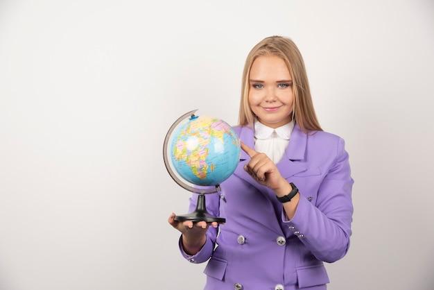 Enseignante pointant sur globe sur blanc.