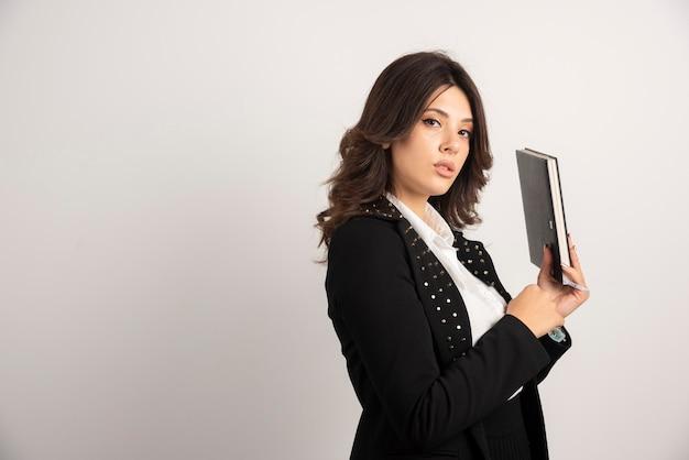 Enseignante posant avec un livre sur blanc.