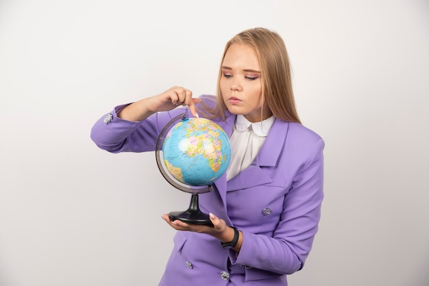 Enseignante regardant globe sur blanc.
