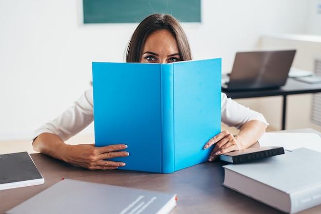 Enseignante se cachant le visage derrière le livre