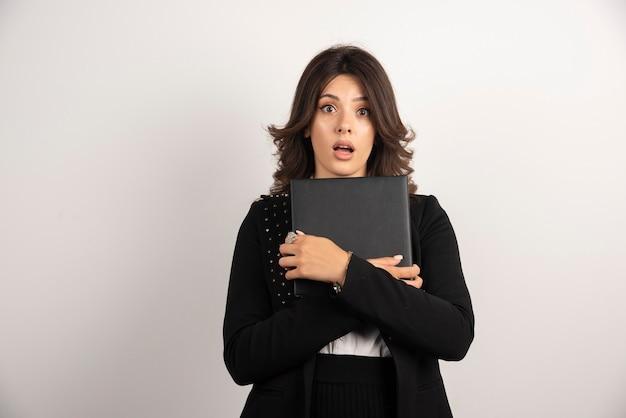Enseignante tenant un livre avec une expression choquée.