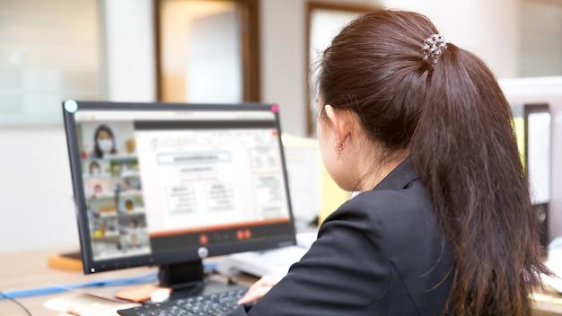 Une enseignante utilise un ordinateur de bureau pour enseigner aux étudiants en ligne