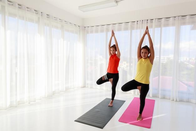 Une enseignante de yoga asiatique dirige et forme une nouvelle étudiante à pratiquer la leçon de yoga de base pendant les cours.