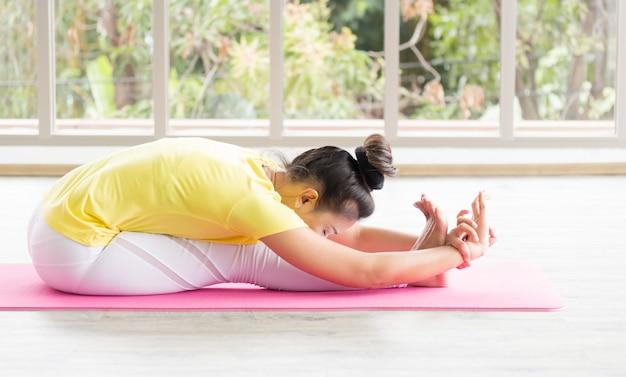 Une enseignante de yoga asiatique portant une chemise jaune entraîne son corps à être fort et en bonne santé grâce au yoga.