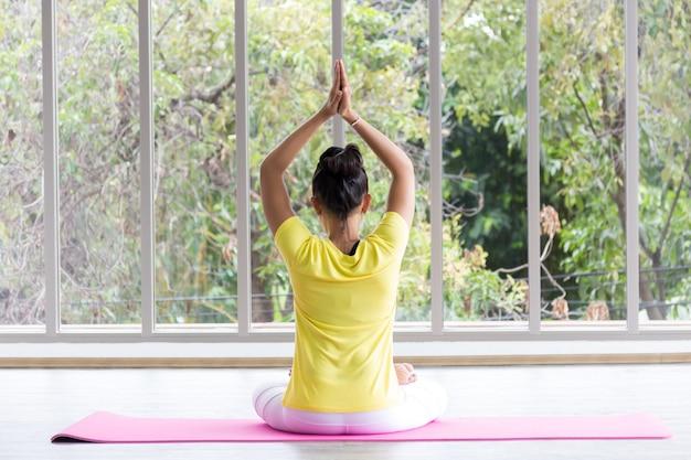 Une enseignante de yoga asiatique portant une chemise jaune entraîne son corps