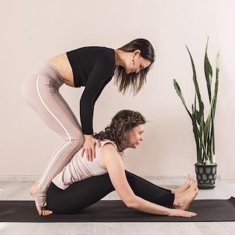 Une enseignante de yoga universel effectue une traction de traction de la colonne vertébrale à un élève assis sur un tapis près du mur