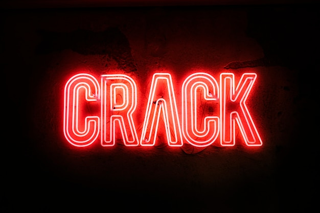 Enseigne au néon sur un mur cassé - crack