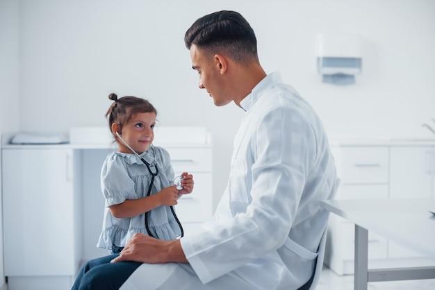 Enseigne à la fille comment utiliser le stéthoscope. un jeune pédiatre travaille avec une petite visiteuse à la clinique.