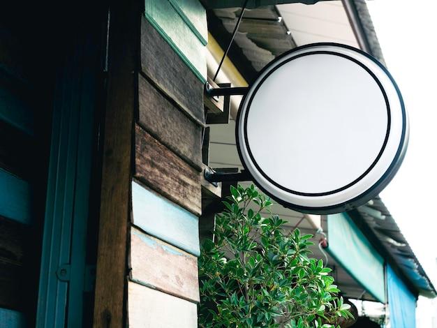 Enseigne de magasin vierge blanche ronde. maquette de la signalisation de la boîte à lumière suspendue en cercle devant le restaurant, montée sur le vieux mur en bois vintage. modèle de panneau de rue.