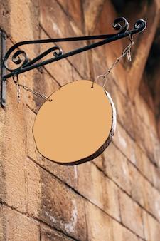 Enseigne vierge en bois rond accroché sur des chaînes sur une broche forgée sur un mur de pierre antique