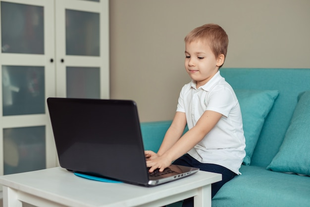 Enseignement à distance à domicile des enfants pendant la quarantaine. heureux, petit garçon, dans, blanc, polo, devoirs, utilisation, ordinateur portable, séance canapé