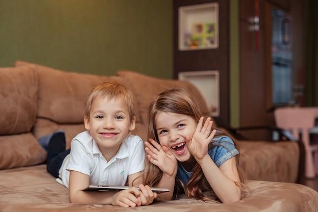 Enseignement à distance à domicile. frère et sœur jumeaux étudient à la maison à l'aide d'une tablette. ils sont heureux et rient en étant allongés sur le canapé