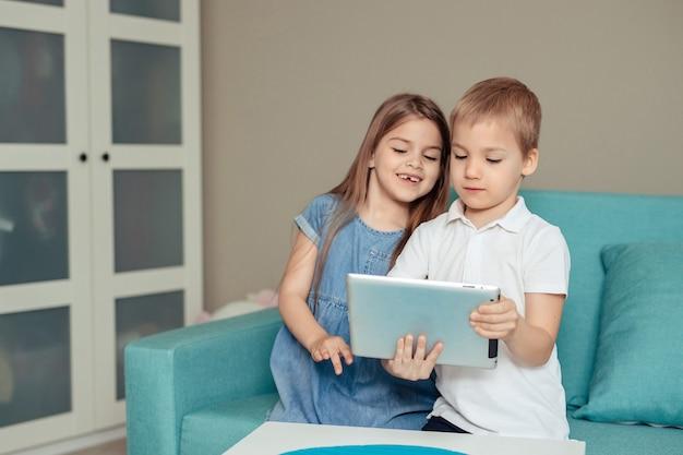 Enseignement à distance à domicile. frères et sœurs jumeaux étudient à la maison à l'aide d'une tablette