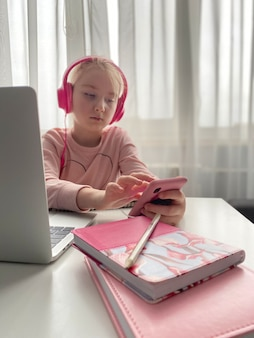 L'enseignement à distance. une écolière au casque rose étudie ses devoirs pendant leur leçon en ligne à la maison via internet. distance sociale pendant la quarantaine