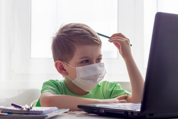 Enseignement à distance, éducation en ligne. distance sociale, auto-isolement pendant la quarantaine. enfant d'âge préscolaire ou écolier en masque médical étudier à la maison avec un ordinateur portable, faire ses devoirs pour l'école de développement