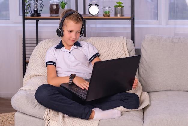 L'enseignement à distance l'éducation en ligne un écolier étudie à la maison et fait ses devoirs à l'école un hom