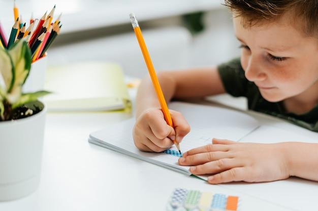 Enseignement à distance éducation en ligne sourire caucasien enfant garçon étudiant à la maison avec un livre écrit en