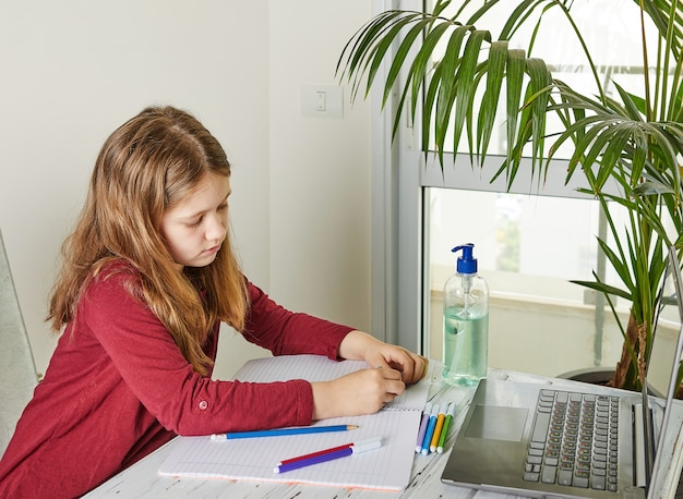 Enseignement à distance en ligne. écolière étudie à la maison avec un ordinateur portable et fait ses devoirs. livres d'entraînement et feutres colorés sur la table, gel avec de l'alcool à 70 pour cent