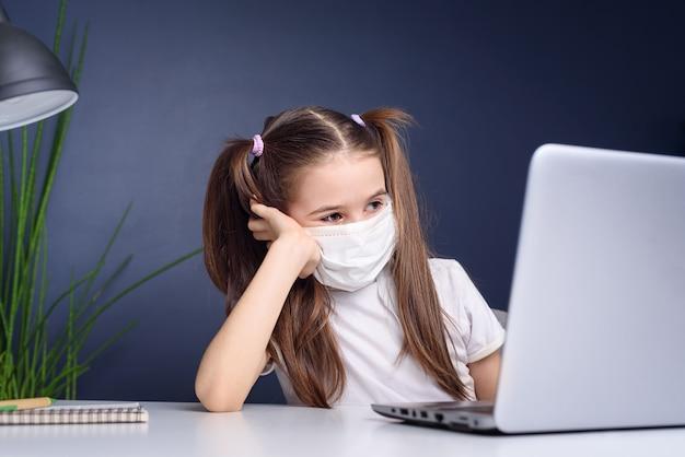 Enseignement à distance en ligne. écolière en masque médical étudie à la maison, travaille sur un ordinateur portable et fait ses devoirs. concept de quarantaine de coronavirus