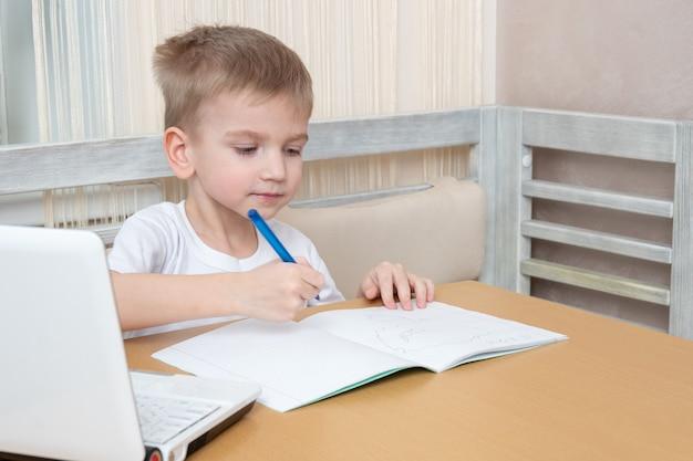 Enseignement à distance en ligne. garçon concentré faisant une leçon de professeur à la maison. un enfant tenant un stylo et dessinant dans un cahier à table avec un ordinateur portable. retour au concept de l'école.