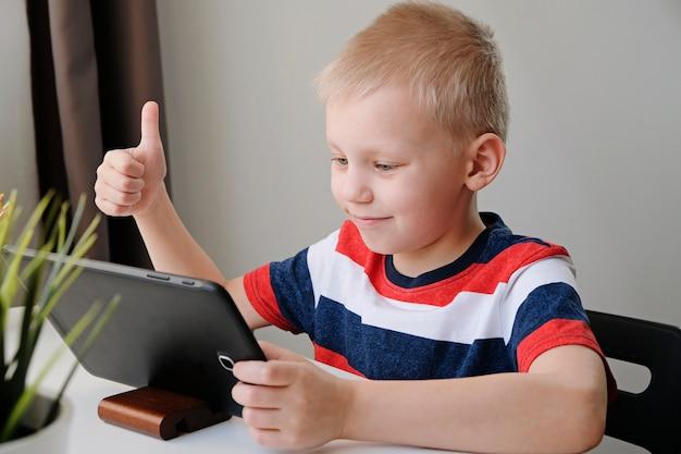 Enseignement à distance en ligne. mignon, caucasien, garçon, devoirs, à, tablette pc, chez soi