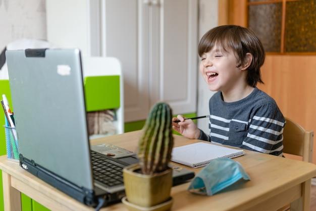 Enseignement à distance pour les enfants pendant l'épidémie de coronavirus. un garçon est assis à une table et effectue les tâches d'un enseignant sur internet.