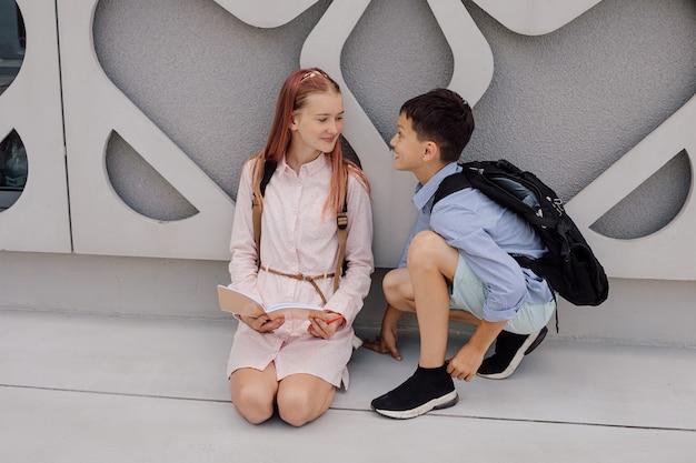 Enseignement secondaire primaire, école, concept d'amitié - deux étudiants garçon et adolescente avec des sacs à dos sont assis, parlent après l'école