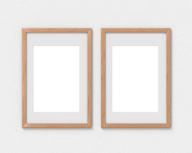 Ensemble de 2 maquettes de cadres en bois verticaux avec une bordure accrochée au mur. base vide pour image ou texte. rendu 3d.