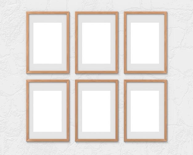 Ensemble de 6 maquettes de cadres en bois verticaux avec une bordure accrochée au mur. base vide pour image ou texte. rendu 3d.