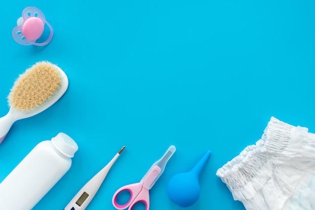 Un ensemble d'accessoires et de cosmétiques pour l'hygiène du bébé, mise en page à plat, vue de dessus, espace de copie pour le texte.