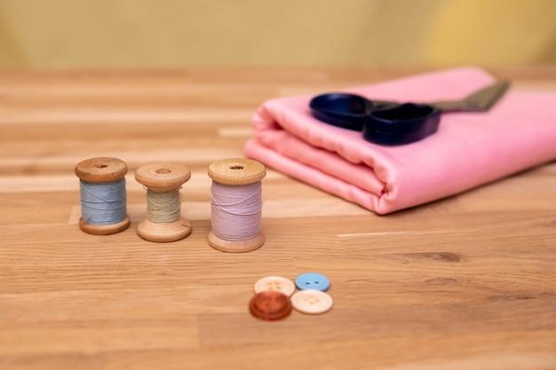 Ensemble d'accessoires de couture. gros plan d'une pile de tissu rose plié, ciseaux à coudre et bobines de fil
