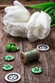 Ensemble d'accessoires de couture à partir de fils et de boutons sur le fond de tulipes blanches