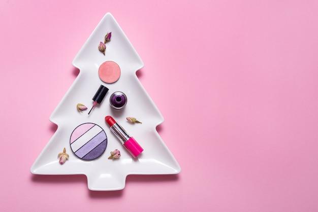 Ensemble d'accessoires de maquillage sur l'arbre de noël, copie espace, fond rouge