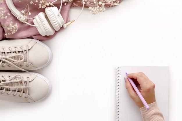 Ensemble d'accessoires de mode femme rose. sneakers, écouteurs et fleurs.