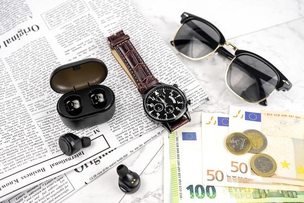 Ensemble d'accessoires pour homme d'affaires avec montre-bracelet, monnaie en euros, journal, écouteurs sans fil, lunettes de soleil. ensemble élégant de trucs de mode sur une table en marbre