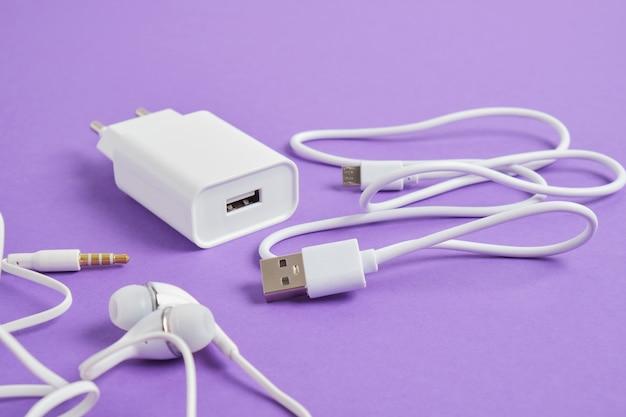 Ensemble d'accessoires pour smartphone, chargeur et écouteurs sur la vue de dessus de l'espace de copie de fond violet