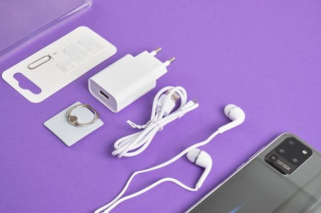 Un ensemble d'accessoires pour un smartphone, un téléphone, un chargeur, un casque, un porte-bague, des adaptateurs pour cartes sim sur fond violet, vue de dessus