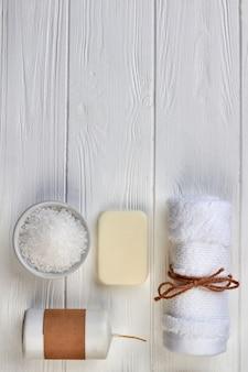 Ensemble d'accessoires de spa sur un bureau en bois blanc. savon vertical avec sel, bougie et serviette.