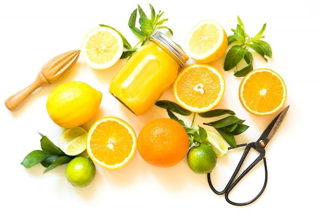 Ensemble d'agrumes sur fond blanc, mise à plat. vue de dessus sur les oranges, les citrons, le citron vert et la menthe. vue de dessus.