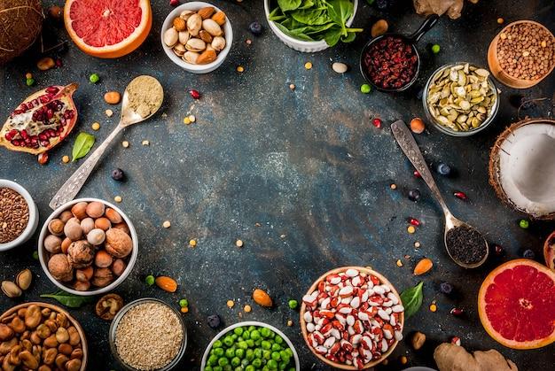 Ensemble d'aliments diététiques sains biologiques, superaliments - haricots, légumineuses, noix, graines, légumes verts, fruits et légumes. vue de dessus de l'espace copie fond bleu foncé