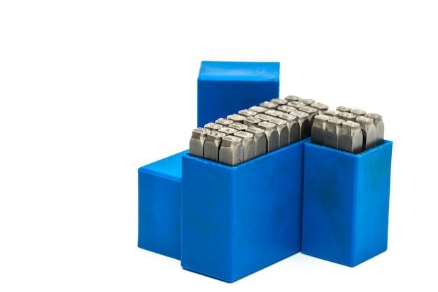 Ensemble d'alphabet de timbre en métal et poinçon dans une boîte en plastique bleue isolé sur fond blanc avec espace de copie