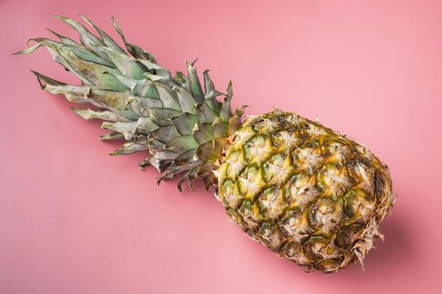 Ensemble d'ananas ou d'ananas jaunes, sur fond d'été texturé rose, avec espace de copie pour le texte